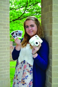Senior Lauren Mueller holding her polaroid and photos.