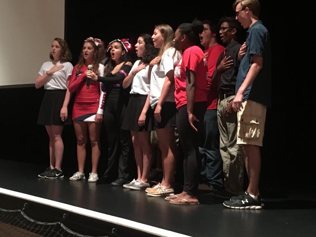 Chorus members singing the National Anthem.